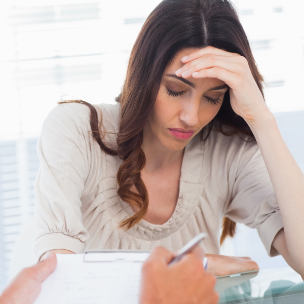 Upset woman listening to her docter talking about a illness in medical office