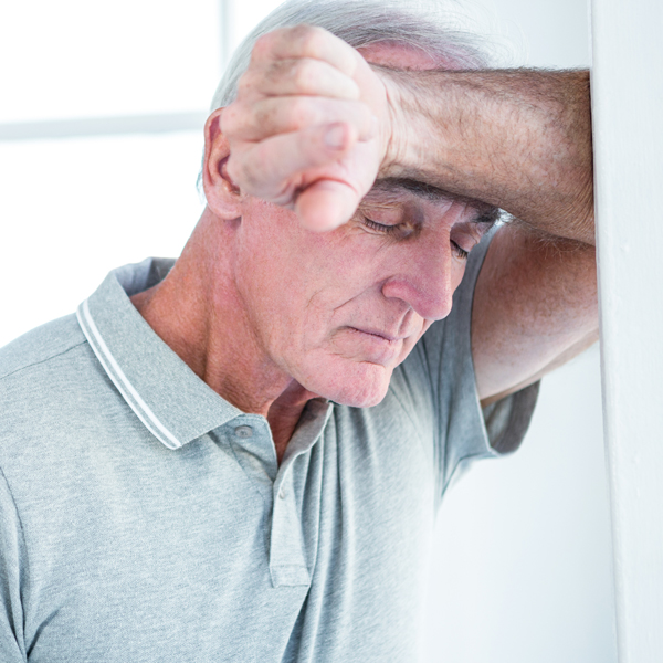 Sad mature man leaning on wall at home