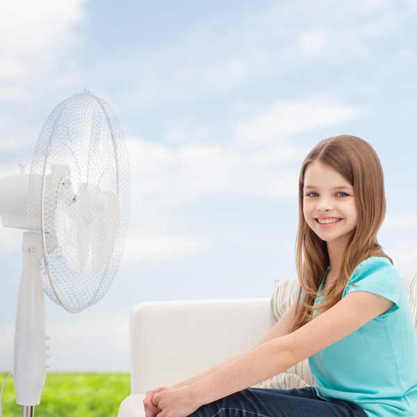smiling little girl with big fan at home