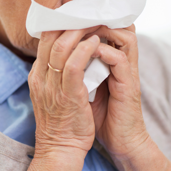 sick senior woman blowing nose to paper napkin