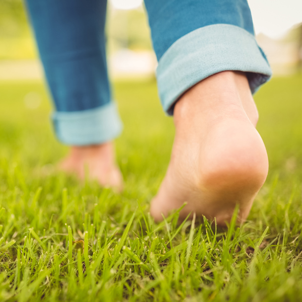 Low section of woman walking on grass in park