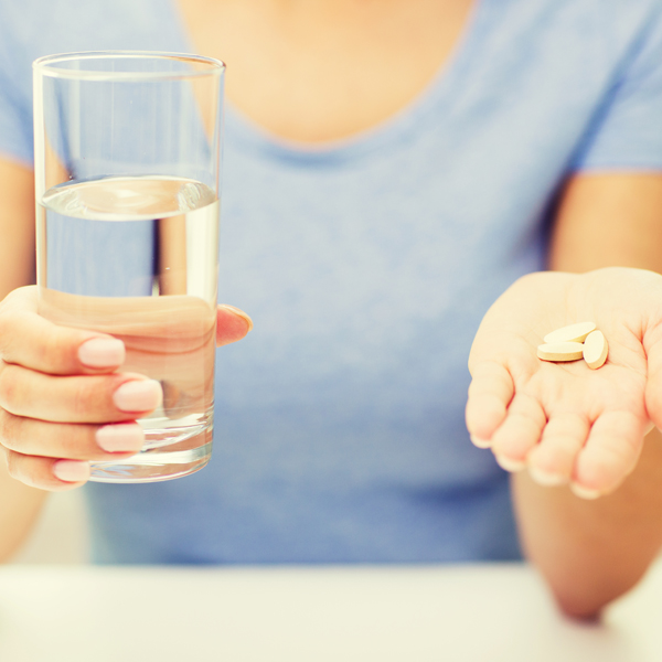 close up of woman hands with pills and water