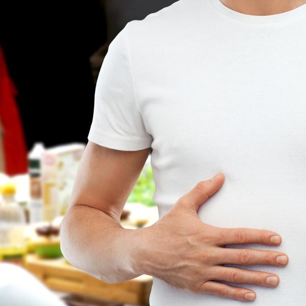 happy full man touching tummy over kitchen